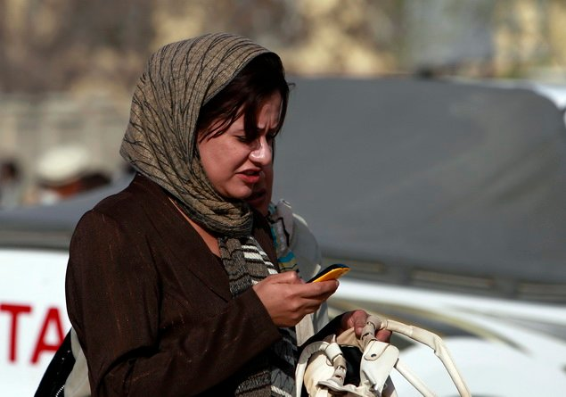 An Afghan woman receives a phone call on her mobile phone on a street in Kabul